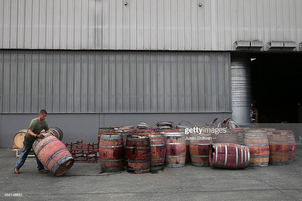 Jey Gonzalez moves a broken wine barrel after it collapsed at a wine barrel storage facility on August 25, 2014 in Napa, California. A day after a 6.0 earthquake rocked the Napa Valley, residents and wineries are continuing clean up operations.