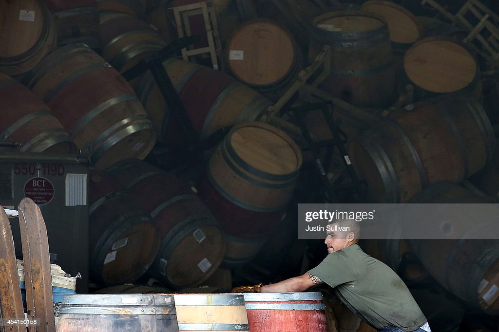 Jey Gonzalez moves a broken wine barrel as he helps clean up a massive collapse at a wine barrel storage facility on August 25, 2014 in Napa, California. A day after a 6.0 earthquake rocked the Napa Valley, residents and wineries are continuing clean up operations.