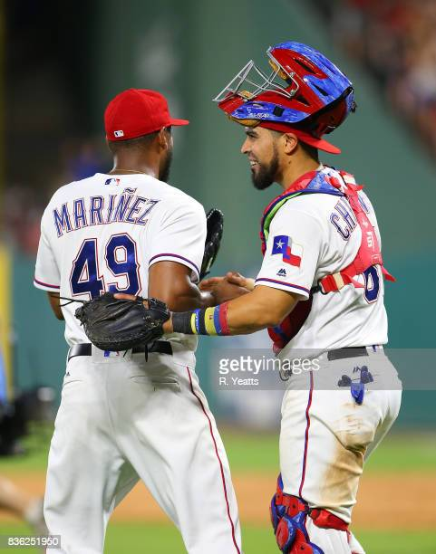 Jhan Marinez of the Texas Rangers is congratulated by Robinson Chirinos for closing out the game for the win against the Chicago White Sox at Globe...