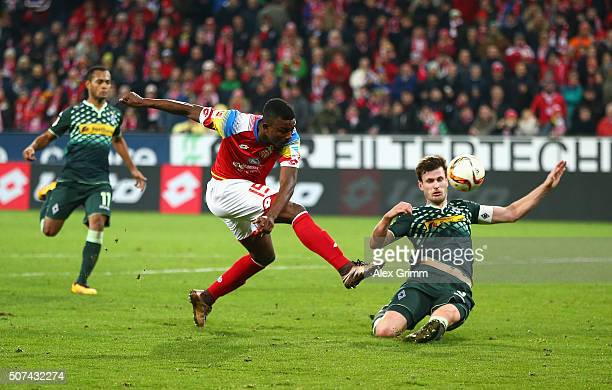 Jhon Andres Cordoba of FSV Mainz shoots as he is challenged by Havard Nordtveit of Borussia Moenchengladbach during the Bundesliga match between 1...