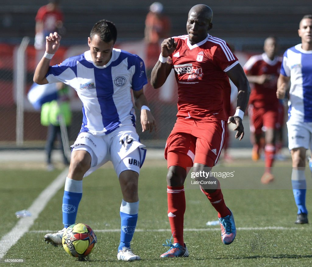 Jhon Cordoba (R) of America de Cali struggles for the ball with David Uribe of Rionegro during a match between America de Cali and Rionegro as part of Torneo Postobon 2014 at Tulio Ospina Stadium on April 05, 2014 in Bello, Colombia.