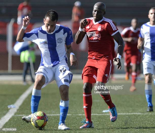 Jhon Cordoba of America de Cali struggles for the ball with David Uribe of Rionegro during a match between America de Cali and Rionegro as part of...
