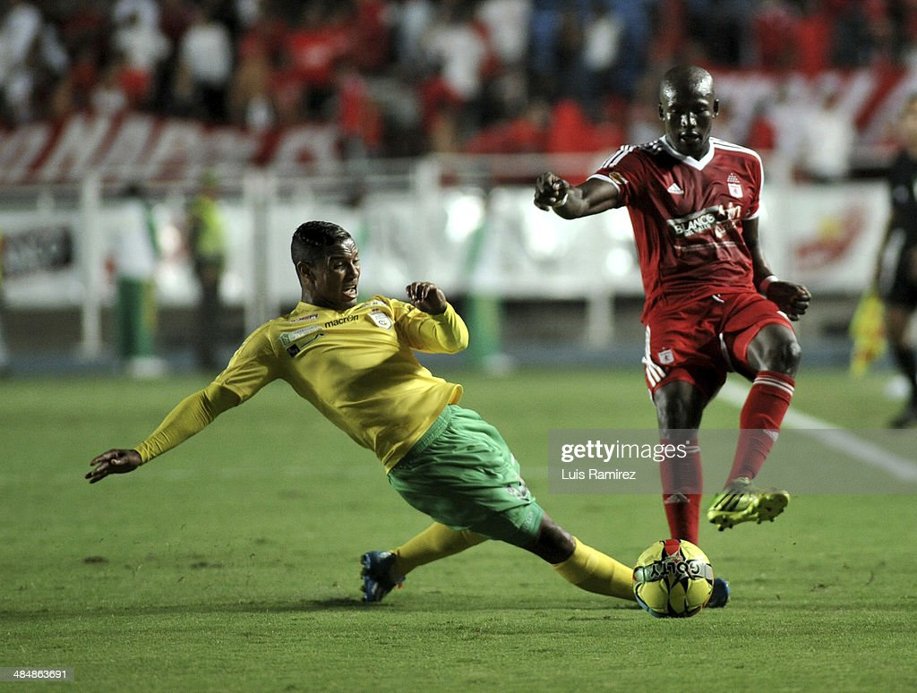 Jhon Cordoba of America de Cali struggles for the ball with Olger Valencia of Real Cartagena during a match between America de Cali and Real Cartagena as part of Torneo Postobon 2014 at Pascual Guerrero Stadium on April 14, 2014 in Cali, Colombia.