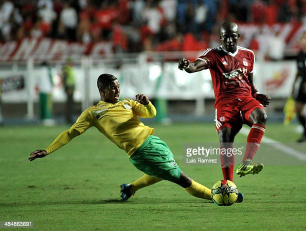 Jhon Cordoba of America de Cali struggles for the ball with Olger Valencia of Real Cartagena during a match between America de Cali and Real...