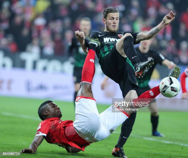 Jhon Cordoba of Mainz is challenged by Jeffrey Gouweleeuw of Augsburg during the Bundesliga match between 1 FSV Mainz 05 and FC Augsburg at Opel...
