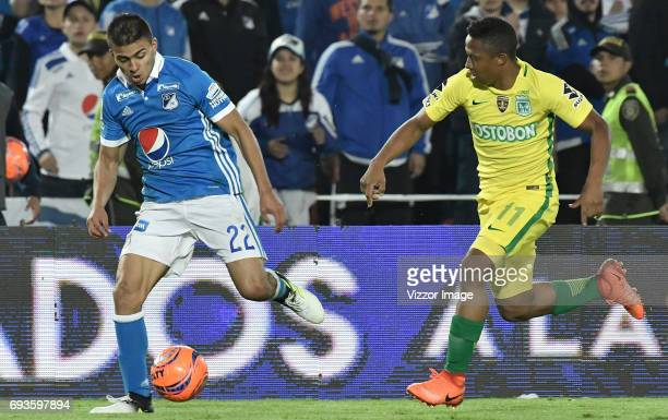 Jhon Duque Arias of Millonarios fights for the ball with Andres Ibarguen of Atletico Nacional during the Semi Finals first leg match between...
