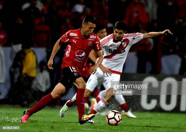 Jhon Hernandez of Deportivo Independiente Medellin vies for the ball with Lucas Martinez of River Plate during a group stage match between Deporivo...