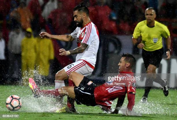 Jhon Hernandez of Deportivo Independiente Medellin vies for the ball with Ariel Rojas of River Plate during a group stage match between Deporivo...