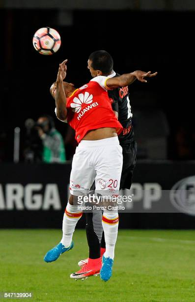 Jhon Pajoy of Santa Fe and Paulo Da Silva of Libertad jump for a header during a second leg match between Independiente Santa Fe and Libertad as part...