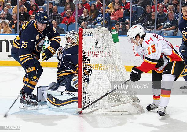 Jhonas Enroth and Rasmus Ristolainen of the Buffalo Sabres defend the net against Johnny Gaudreau of the Calgary Flames at First Niagara Center on...