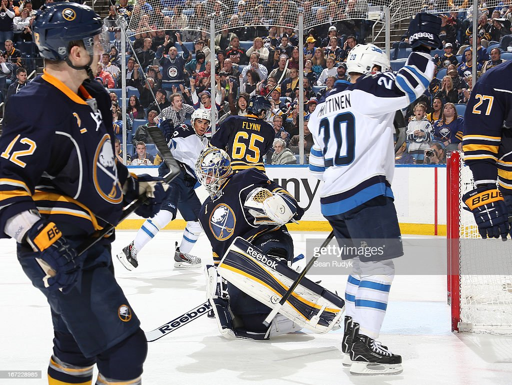 Jhonas Enroth #1 of the Buffalo Sabres looks down in frustration as Antti Miettinen #20 of the Winnipeg Jets celebrates his goal with teammate Alexander Burmistrov #8 at First Niagara Center on April 22, 2013 in Buffalo, New York.