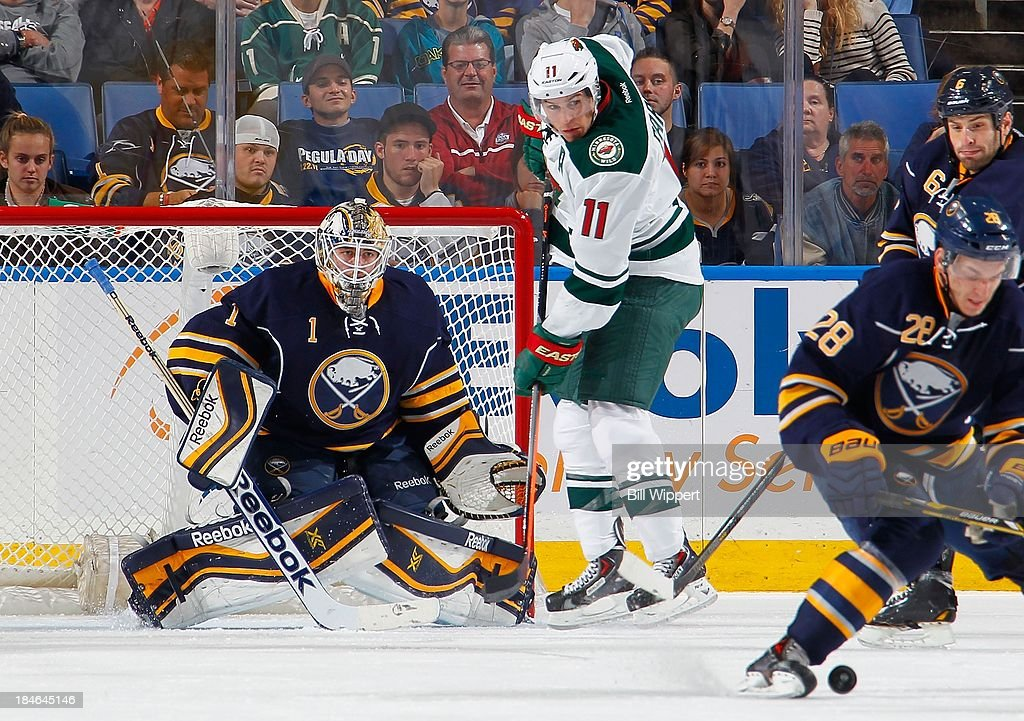 <a gi-track='captionPersonalityLinkClicked' href=/galleries/search?phrase=Jhonas+Enroth&family=editorial&specificpeople=570456 ng-click='$event.stopPropagation()'>Jhonas Enroth</a> #1 of the Buffalo Sabres looks for the puck alongside <a gi-track='captionPersonalityLinkClicked' href=/galleries/search?phrase=Zach+Parise&family=editorial&specificpeople=213606 ng-click='$event.stopPropagation()'>Zach Parise</a> #11 of the Minnesota Wild on October 14, 2013 at the First Niagara Center in Buffalo, New York. Minnesota won, 2-1.