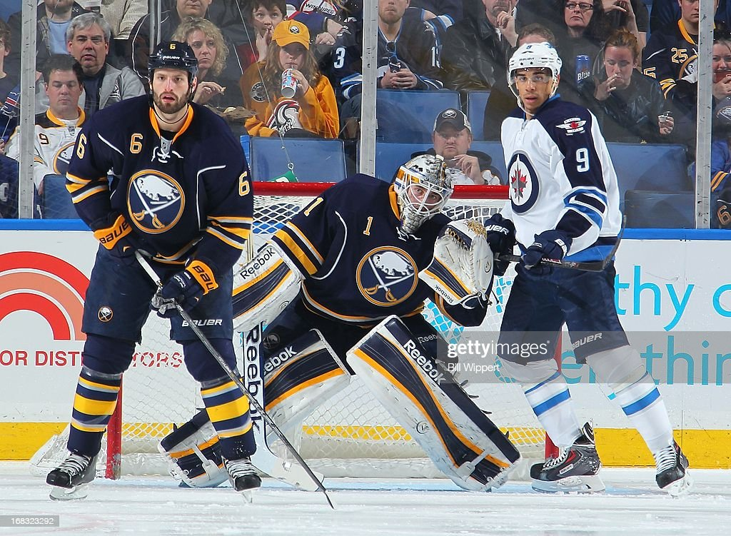 Jhonas Enroth #1 of the Buffalo Sabres looks for the puck between teammate Mike Weber #6 and Evander Kane #9 of the Winnipeg Jets on April 22, 2013 at the First Niagara Center in Buffalo, New York.