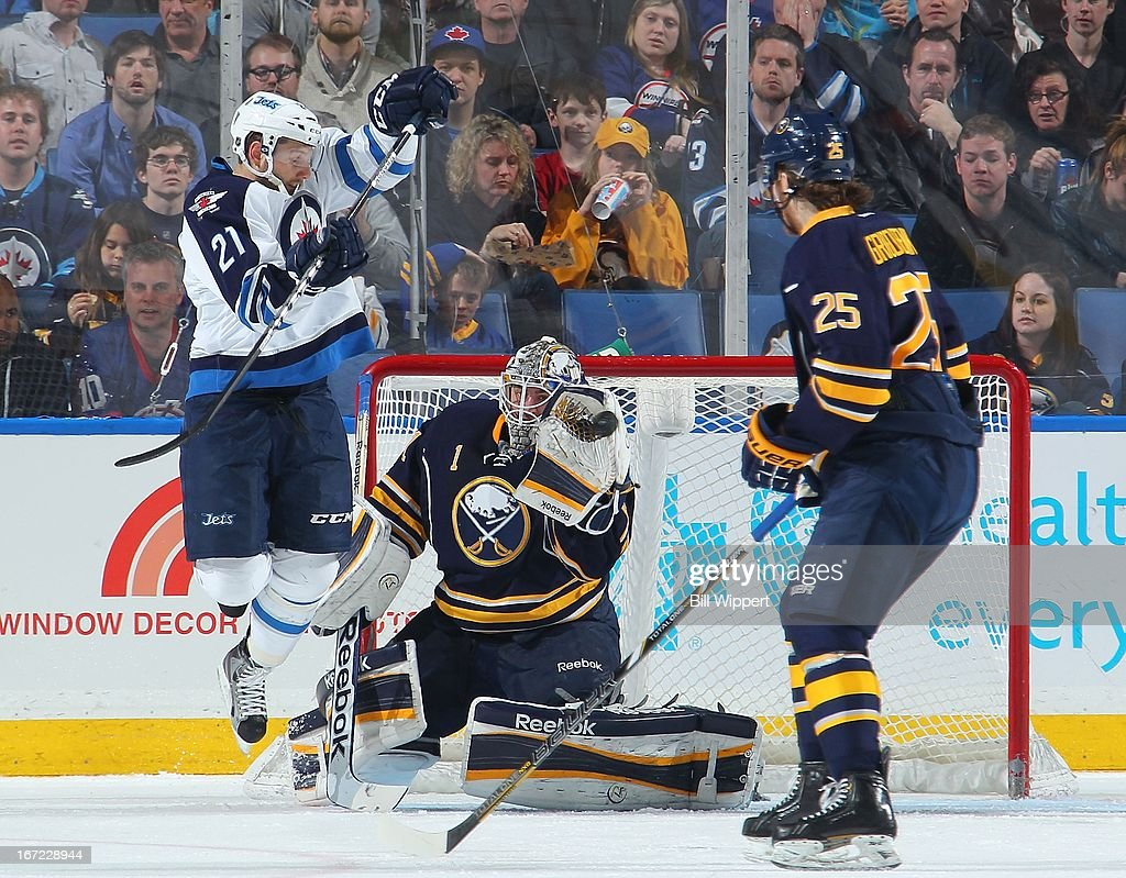 Jhonas Enroth #1 of the Buffalo Sabres makes a glove save alongside teammate Mikhail Grigorenko #25 and Aaron Gagnon #21 of the Winnipeg Jets on April 22, 2013 at the First Niagara Center in Buffalo, New York. Winnipeg defeated Buffalo, 2-1.