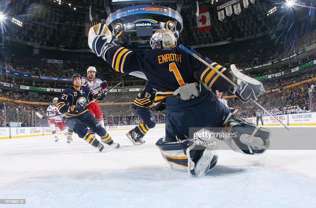 Jhonas Enroth #1 of the Buffalo Sabres reaches to make a glove save in front of teammate Adam Pardy #27 and Taylor Pyatt #14 of the New York Rangers on April 19, 2013 at the First Niagara Center in Buffalo, New York.