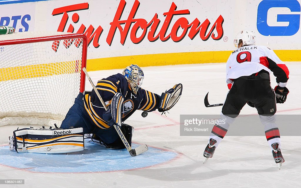 <a gi-track='captionPersonalityLinkClicked' href=/galleries/search?phrase=Jhonas+Enroth&family=editorial&specificpeople=570456 ng-click='$event.stopPropagation()'>Jhonas Enroth</a> #1 of the Buffalo Sabres stops <a gi-track='captionPersonalityLinkClicked' href=/galleries/search?phrase=Milan+Michalek&family=editorial&specificpeople=544987 ng-click='$event.stopPropagation()'>Milan Michalek</a> #9 of the Ottawa Senators in the shootout at First Niagara Center on December 31, 2011 in Buffalo, New York. Ottawa won 3-2 in the shootout.