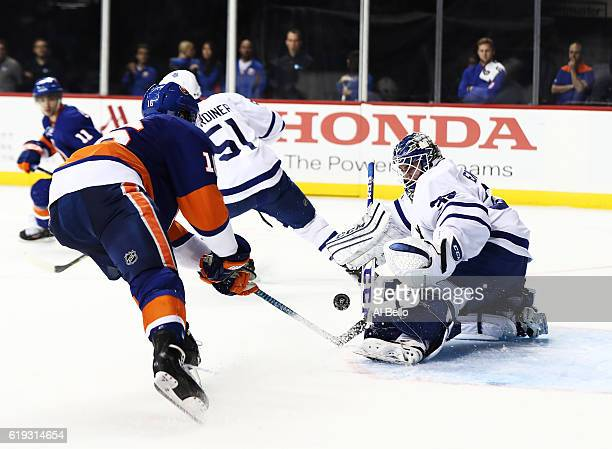 Jhonas Enroth of the Toronto Maple Leafs makes a save against Andrew Ladd of the New York Islanders during their game at the Barclays Center on...