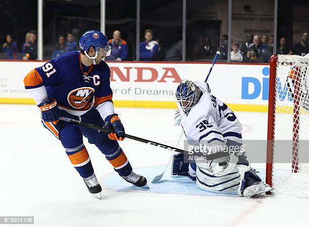 Jhonas Enroth of the Toronto Maple Leafs makes a save against John Tavares of the New York Islanders during their game at the Barclays Center on...