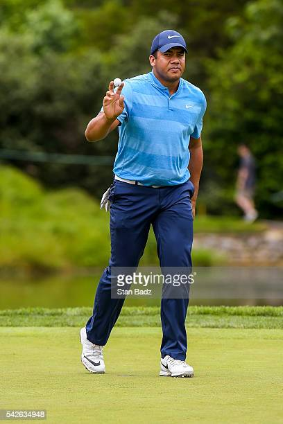 Jhonattan Vegas of Venezuela waves his ball to fans after making a birdie putt on the 18th hole green during the first round of the Quicken Loans...