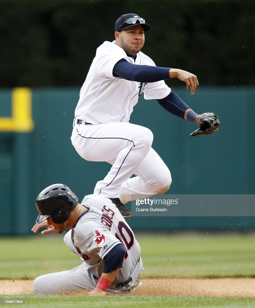 <a gi-track='captionPersonalityLinkClicked' href=/galleries/search?phrase=Jhonny+Peralta&family=editorial&specificpeople=213286 ng-click='$event.stopPropagation()'>Jhonny Peralta</a> #27 of the Detroit Tigers avoids <a gi-track='captionPersonalityLinkClicked' href=/galleries/search?phrase=Yan+Gomes&family=editorial&specificpeople=9004037 ng-click='$event.stopPropagation()'>Yan Gomes</a> #10 of the Cleveland Indians to turn a double play on Michael Brantley at first base in the seventh inning at Comerica Park on May 12, 2013 in Detroit, Michigan.