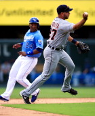 Jhonny Peralta of the Detroit Tigers barehands the ball and throws toward first as Miguel Tejada of the Kansas City Royals advances to second during...