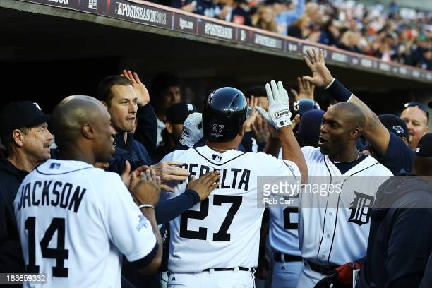Jhonny Peralta of the Detroit Tigers celebrates with teammates in the dugout after hitting a three run home run in the fifth inning against the...