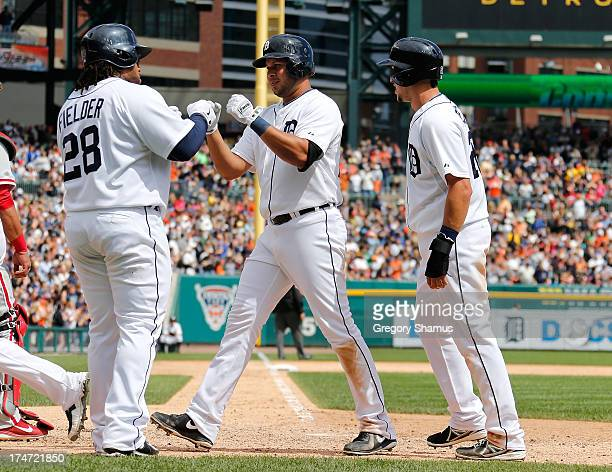 Jhonny Peralta of the Detroit Tigers is welcomed to home plate after his sixth inning grand slam home run by teammates Hernan Perez and Prince...