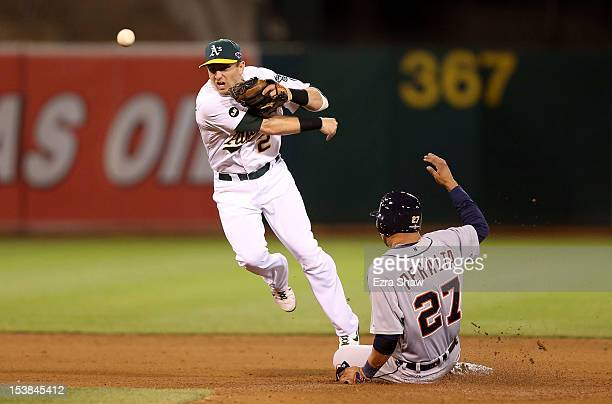 Jhonny Peralta of the Detroit Tigers slides into second base and is out as Cliff Pennington of the Oakland Athletics throws to first base trying to...