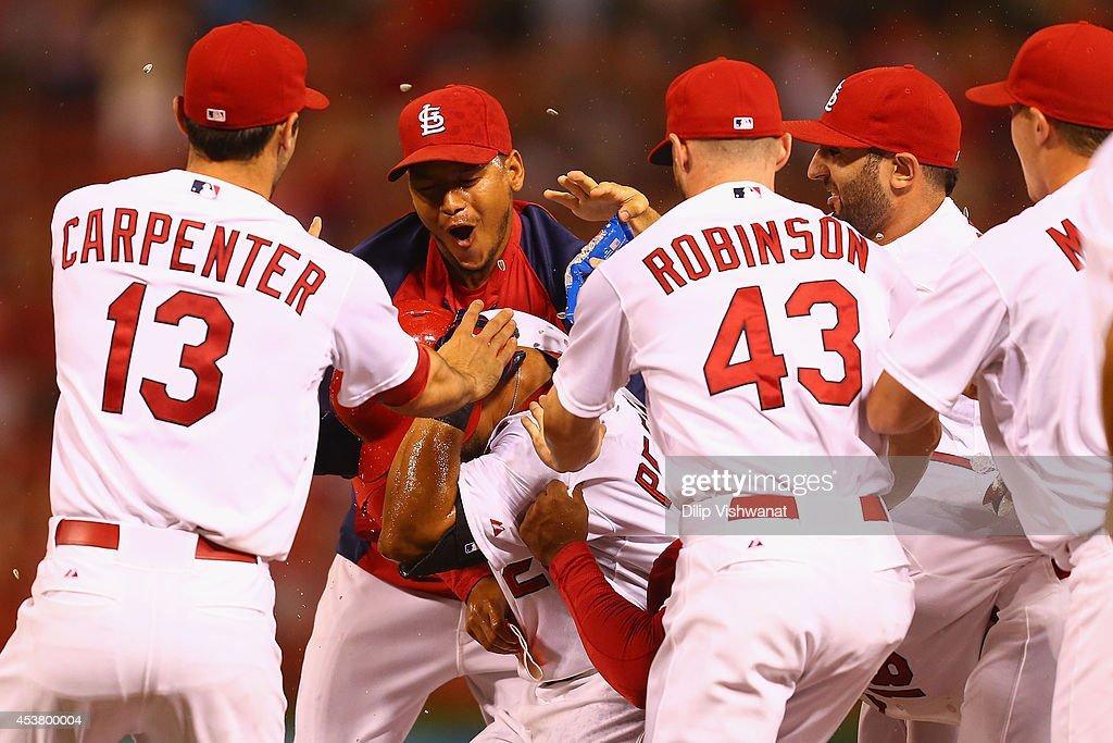 <a gi-track='captionPersonalityLinkClicked' href=/galleries/search?phrase=Jhonny+Peralta&family=editorial&specificpeople=213286 ng-click='$event.stopPropagation()'>Jhonny Peralta</a> #27 of the St. Louis Cardinals celebrates with <a gi-track='captionPersonalityLinkClicked' href=/galleries/search?phrase=Yadier+Molina&family=editorial&specificpeople=172002 ng-click='$event.stopPropagation()'>Yadier Molina</a> #4 and other teammates after hitting the game-winning RBI single at Busch Stadium on August 18, 2014 in St. Louis, Missouri. The Cardinals beat the Reds in 10 innings.