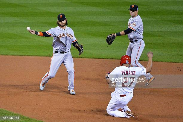 Jhonny Peralta of the St Louis Cardinals is out at second as Brandon Crawford of the San Francisco Giants turns the double play on a ball hit by...