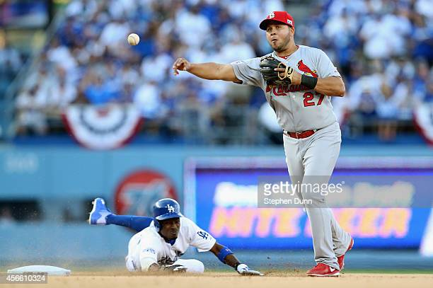 Jhonny Peralta of the St Louis Cardinals throws to first after forcing out Dee Gordon of the Los Angeles Dodgers at second base but is too late to...