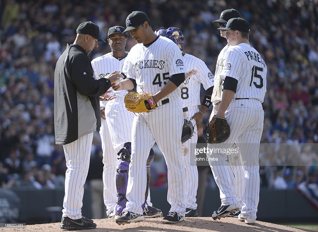 Jhoulys Chacin (45) of the Colorado Rockies hands the baseball to manager Walt Weis in the seventh inning against the San Diego Padres April 7, 2013 at Coors Field. Chacin was the winning pitcher as the Rockies defeated the Padres 9-1.
