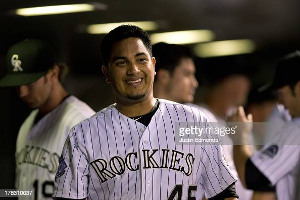 Jhoulys Chacin of the Colorado Rockies smiles in the dugout after the seventh inning against the San Francisco Giants at Coors Field on August 28...