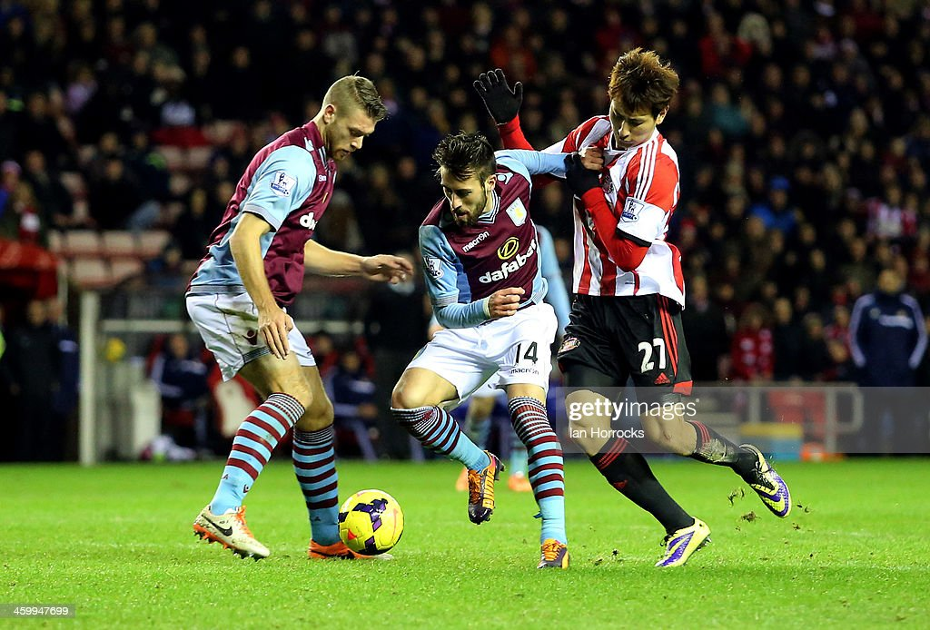 Ji Dong Won of Sunderland (R) tries to tackle Antonio Luna of Aston Villa (C) with Nathan Baker (L) watching during the Barclays Premier League match between Sunderland and Aston Villa at The Stadium of Light on January 01, 2014 in Sunderland, England.