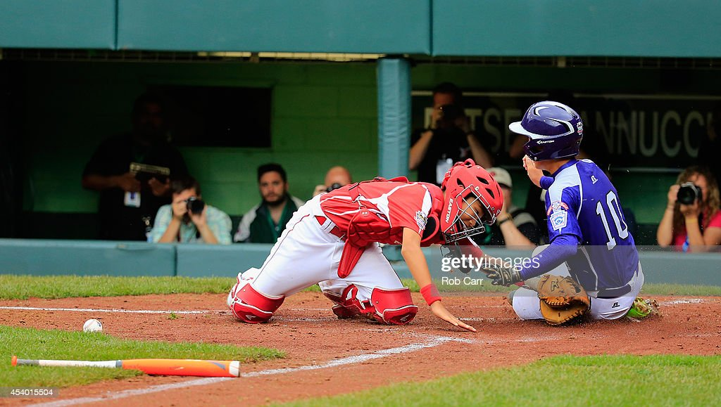 Ji Ho Park #10 of Team Asia-Pacific scores a run as catcher Shingo Tomita #8 of Team Japan applies the late tag during the fourth inning of the International Championship game of the Little League World Series at Lamade Stadium on August 23, 2014 in South Williamsport, Pennsylvania.