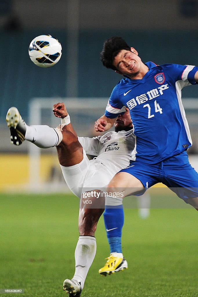 Ji Xiang #24 of Jiangsu Sainty and Pratum Chuthong #3 of Buriram United battle for the ball during the AFC Champions League match between Jiangsu Sainty and Buriram United at Nanjing Olympic Sports Center Stadium on April 2, 2013 in Nanjing, China.