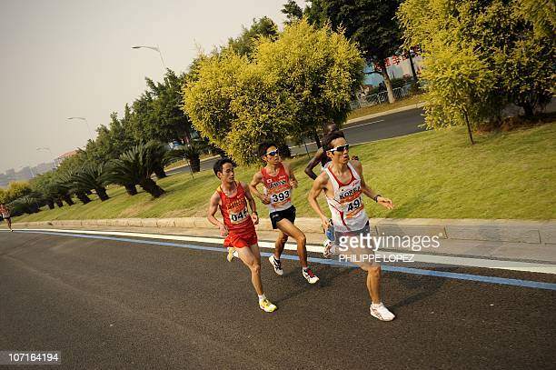 Ji Youngjun of South Korea Yukihiro Kitaoka of Japan and Dong Guojian of China compete in the marathon at the triathlon venue during the16th Asian...