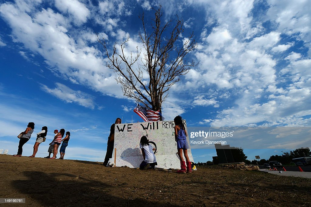 Jia Cummings, 10, (C) and Lucy Cummings, 8, (R) sign a message board at the makeshift memorial for the 12 movie theater shooting victims built across the street from the Century 16 theater, July 24, 2012 in Aurora, Colorado. James Holmes, 24, is suspected of killing 12 and injuring 58 others last Friday during a shooting rampage at a screening of 'The Dark Knight Rises.'