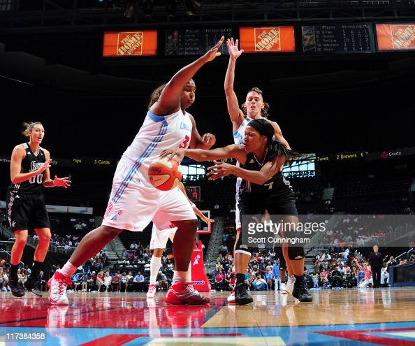 Jia Perkins of the San Antonio Silver Stars passes off against Courtney Paris and Coco Miller of the Atlanta Dream at Philips Arena on June 26 2011...