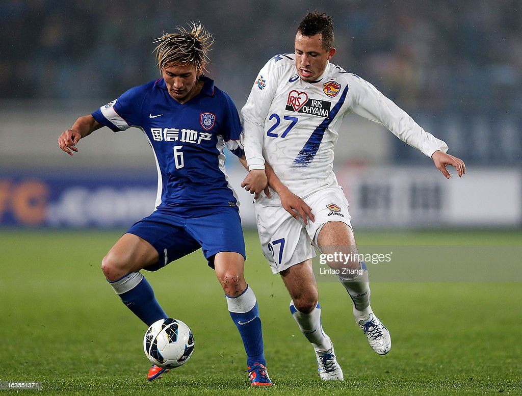 Jiang Jiajun (L) of Jiangsu Sainty challenges Diogo (R) of Vegalta Sendaion during the AFC Champions League match between Jiangsu Sainty and Vegalta Sendai at Nanjing Olympic Sports Center Stadium on March 12, 2013 in Nanjing, China.
