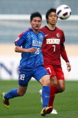 Jiang Jiajun of Shanghai Shenhua and Toru Araiba of Kashima Antlers compete for the ball during the AFC Champions League Group H match between...
