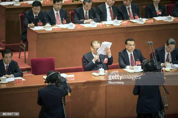 Jiang Zemin China's former president center holds a magnifying glass while reading a report as he sits alongside Li Keqiang China's premier second...