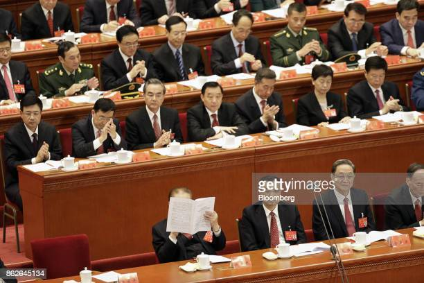 Jiang Zemin China's former president front row from left reads a copy of a report as Li Keqiang China's premier Yu Zhengsheng chairman of the Chinese...
