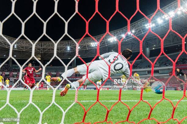 Jiangsu FC Goalkeeper Zhang Sipeng tries to stop a penalty kicked for Shanghai FC Forward Givanildo Vieira De Sousa during the AFC Champions League...