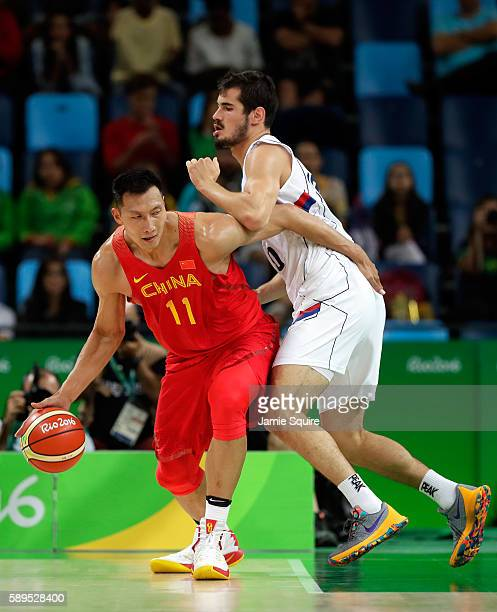 Jianlian Yi of China controls the ball as Nikola Kalinic of Serbia defends during the preliminary round game at the Rio 2016 Olympic Games on August...
