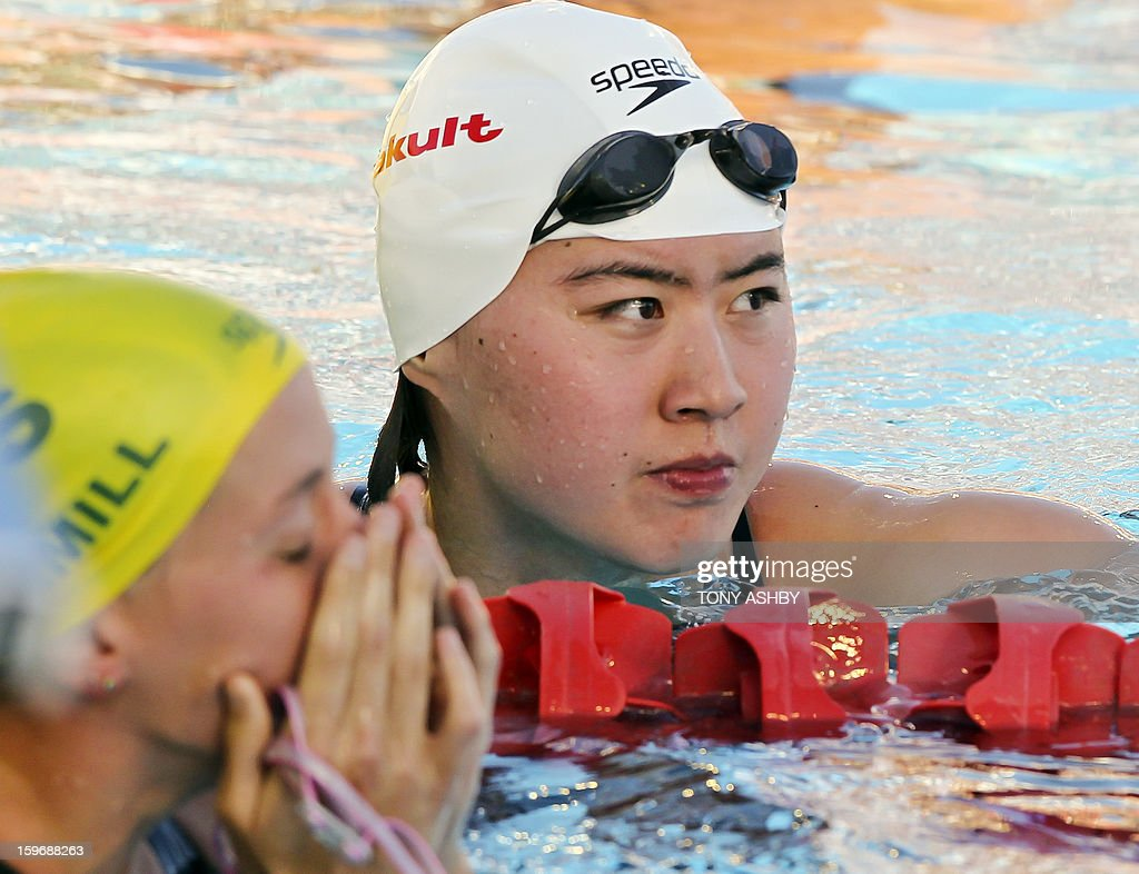 Jiao Liuyang of China (R) reacts after winning the women's 200m butterfly race at the Aquatic Super Series swimming competition in Perth on January 18, 2013. AFP PHOTO / Tony ASHBY USE