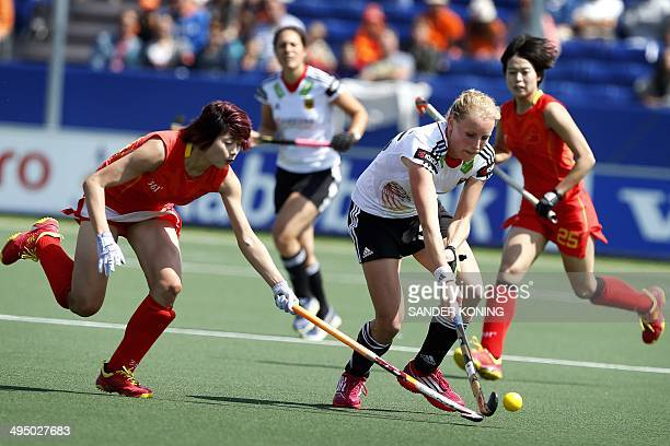 Jiaojiao De of China viers for the ball with Hannah Kruger of Germany during the Field Hockey World Cup 2014 women's tournament group stage match...
