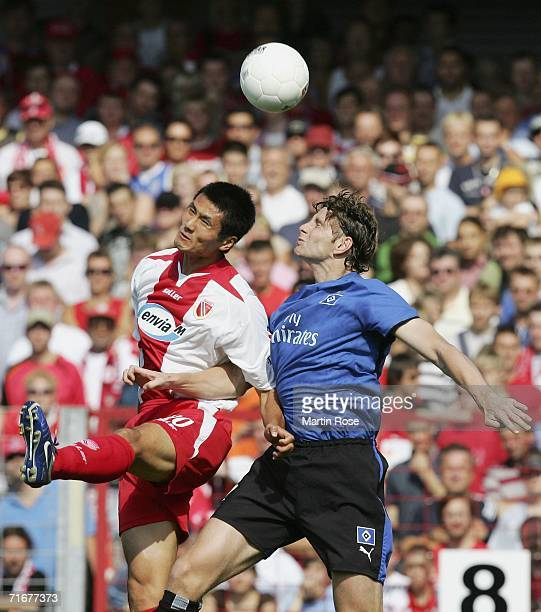 Jiayi Shao of Cottbus and Bastian Reinhardt of Hamburg head for the ball during the Bundesliga match between Energie Cottbus and Hamburger SV at the...