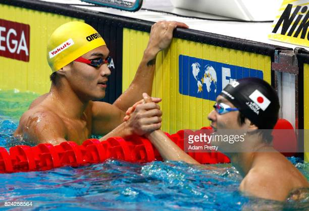 Jiayu Xu of China shakes hands with Junya Koga of Japan during the Men's 50m Backstroke semi final on day sixteen of the Budapest 2017 FINA World...