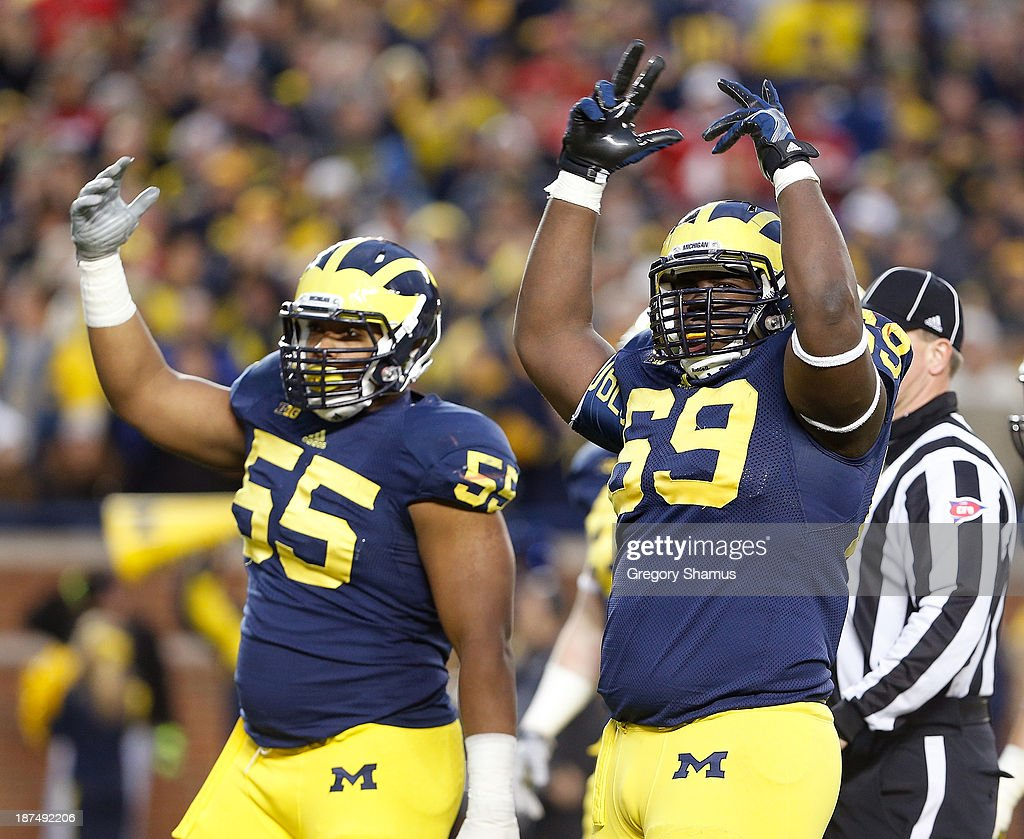 Jibreel Black #55 and Willie Henry #69 of the Michigan Wolverines fire up the crowd in the second quarter at Michigan Stadium on November 9, 2013 in Ann Arbor, Michigan.